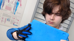 Picture of Jonathan with his Saebo glove, funded by an FTCT grants.