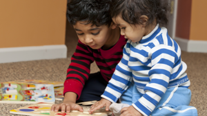 Two small preschool children playing with puzzles.
