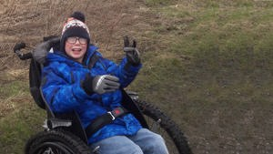 Picture of a young boy in his new wheelchair.
