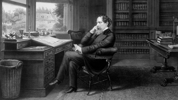 Black and white picture of Charles Dickens sitting at his desk.